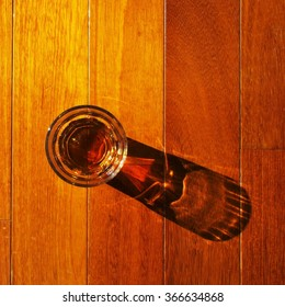 Dram of whiskey and its long shadow on wooden deck