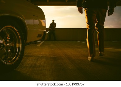 drama and cinematic 70s shot of a silhouette of a man what a jacket and pants walking from his el camino car towards someone wearing a brown leather jacket while waiting in a parking garage