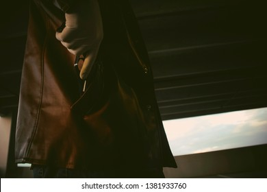 drama and cinematic 70s shot of a silhouette of a man wearing a brown leather jacket while withdrawing a gun from his pocket in a parking garage