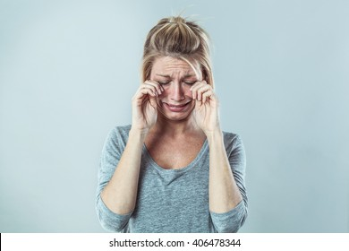 drama concept - gloomy young blond woman crying with big tears expressing failure and disappointment, grey background studio, contrast effects