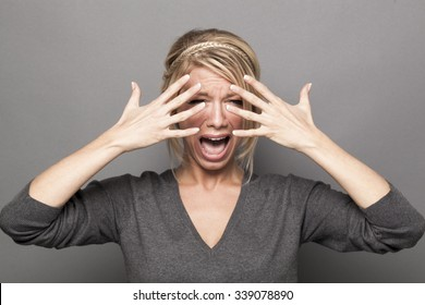 drama queen concept - crying out loud 20s blond girl complaining with tears and hands hiding her face for show,grey background