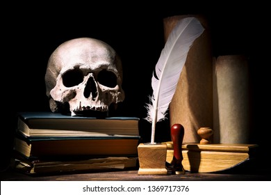 Drama or theater and literature concept. Old inkstand with feather near scrolls with skull on books against black background. Dramatic light