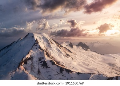 Dramatic Aerial Landscape View of the cloud covered mountains during a vibrant sunset. Artistic Render. Taken near Mount Baker, East of Vancouver and Seattle, Washington, United States.