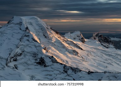 Dramatic Aerial Landscape View of the cloud covered mountains during a vibrant sunset. Taken near Mount Baker, East of Vancouver and Seattle, Washington, United States.