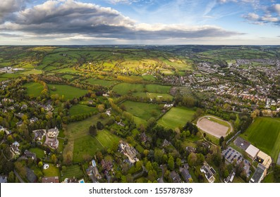 Dramatic aerial view of idyllic rolling patchwork farmland and houses with pretty wooded boundaries, lit in warm early evening sunshine in the heart of the Cotswolds, England, UK.