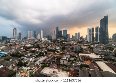 Dramatic aerial view of the sunset over the business district skyline in Jakarta, which contrast with a middle class residential district in the heart of Jakarta, Indonesia capital city