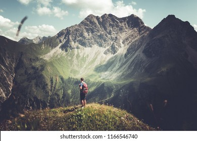 Dramatic alpine landscape with rear view of a lonely man standing on the top of the mountain while admiring the amazing view of the Alps in a summer day in Germany, Europe