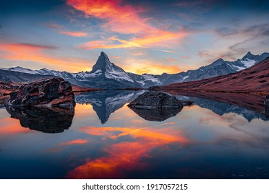 Dramatic Alps scenery. Exciting morning view of Stellisee lake with Matterhorn (Cervino) peak on background. Breathtaking autumn scene of Swiss Alps, Zermatt resort location, Switzerland, Europe.
