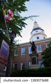 Dramatic angle of the Maryland State House in Annapolis, with the largest wood dome in America. Statue of  Revolutionary war hero, General Baron DeKalb & the Maryland State flag in the foreground.
