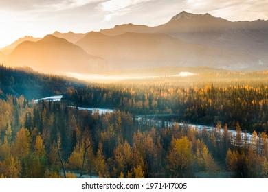 dramatic autumn sunset in the snow capped jagged Chugach mountain range and the beautiful Matanuska River in Alaska.