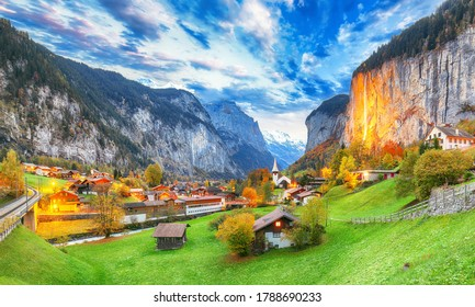 Dramatic autumn view of Lauterbrunnen valley with gorgeous Staubbach waterfall and Swiss Alps at sunset time.  Location: Lauterbrunnen village, Berner Oberland, Switzerland, Europe.