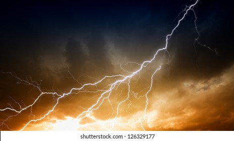 Dramatic background - lightnings in sunset sky with dark clouds