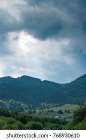 A dramatic beam of sunlight comes from the cloudy skies. A weather is nasty and rainy. A small village is located in a mountain valley. With some small farming fields.