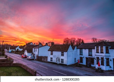 Dramatic and beautiful sunrise illuminating the sky over the quaint white cottages and terrace houses of Monkton, Kent, UK on a quiet winter morning.
