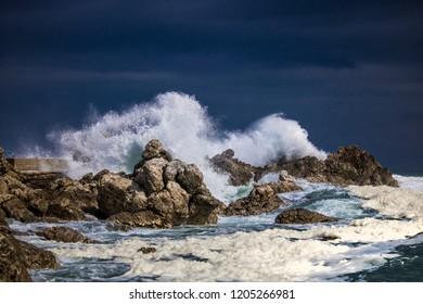 Dramatic big stormy crashing waves splash. Kleinmond, Western Cape, South Africa.