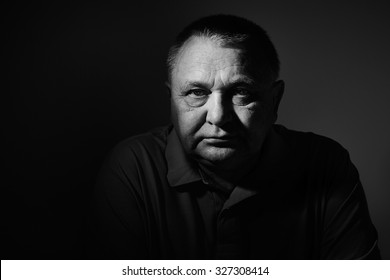 Dramatic black and white close up portrait of aged man sitting and looking at camera against wall - depression concept
