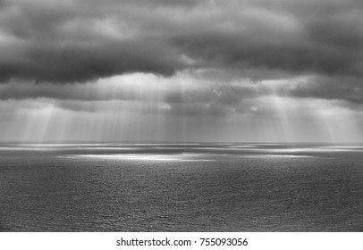 Dramatic black and white cloudy sky with rays of sun shining through onto the sea with space for text.