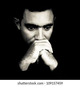 Dramatic black and white face of a worried young man  emerging from a black background