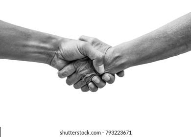 Dramatic black and white help hands holding together representing friendship, partnership, help and hope, donation, assistance. Helping old, poor and hunger.