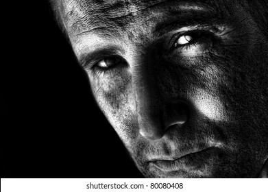 A dramatic black and white image of handsome, confident man staring intently.