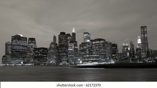 A dramatic black and white photograph of the Downtown Manhattan skyline