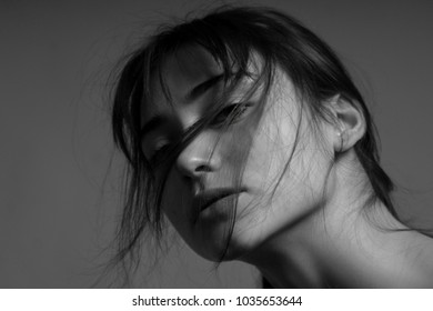 Dramatic black and white portrait of a beautiful lonely girl with freckles isolated on a dark background in studio shot.