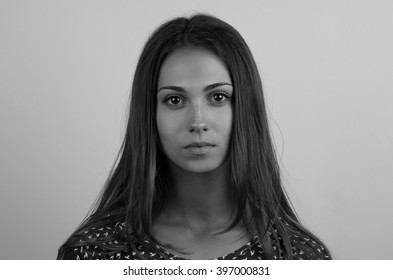 Dramatic black and white portrait of a beautiful lonely girl isolated on a grey background in studio shot