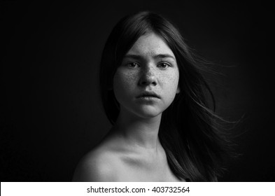 Dramatic black and white portrait of a beautiful girl on a dark background in the studio shot