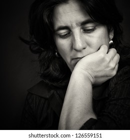 Dramatic black and white portrait of sad and thoughtful woman