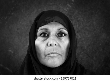Dramatic black and white portrait of serious middle aged muslim woman with black scarf or hijab