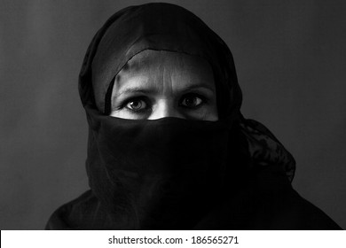 Dramatic black and white portrait of a veiled middle-aged muslim woman with strong gaze