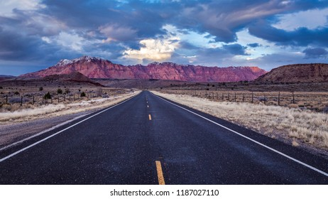 Dramatic blue and pink evening sky frames distant snow-capped pink and red mountains.  Asphalt road leads into frame toward mountains in the distance.  Taken near Shivwits Indian Reservation in Utah