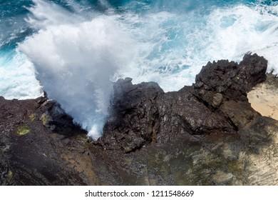 Dramatic close-up shot of water bursting through a natural blowhole along a rocky coast
