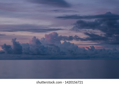Dramatic clouds above wide pacific ocean at sunset