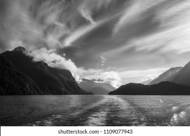 Dramatic clouds and alpine scenery at Lake Manapouri in black and white on a adventure cruise to Doubtful Sound, Fiordland National Park, New Zealand, South Island.