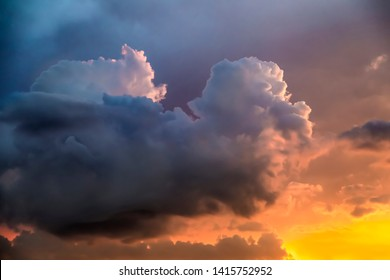 Dramatic clouds float in an intensely colorful sunset sky as stormy weather clears.