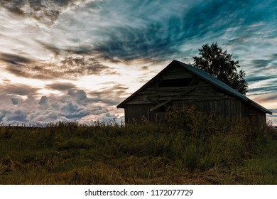 The dramatic clouds gather on the summer sky at the rural Finland. The old barn house is waiting for the harvest time.