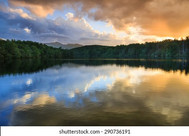 Dramatic clouds lit by the sun at sunset and reflecting in the water of Julian Price Lake off the Blue Ridge Parkway in western North Carolina.