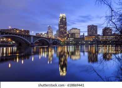 Dramatic Clouds and Minneapolis Cityscape Reflect in Mississippi River at Twilight