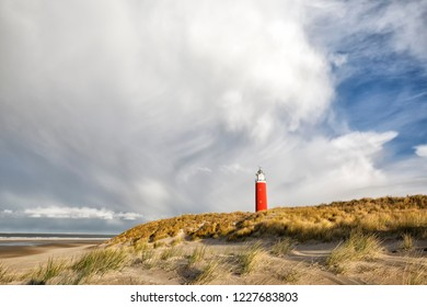 dramatic clouds over red lighthouse on dune, Texel, Netherlands