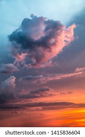Dramatic clouds populate an intensely colorful sunset sky as stormy weather clears.