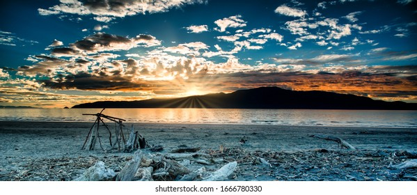 Dramatic cloudscape and Sunset flare over silhouetted Kapiti island at Paraparaumu beach covered in driftwood and beach art