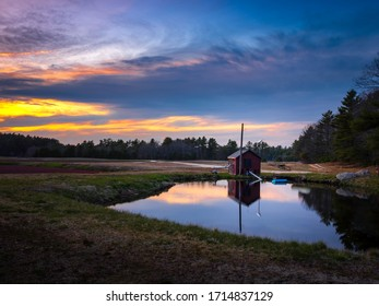 Dramatic cloudscape at sunset and reflections on pumphouse pond at cranberry bog