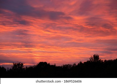 Dramatic cloudy sky. Beautiful red sunset. Very clear and bright perspective with clouds layers that accentuate the horizon, while several sun rays penetrates the clouds.