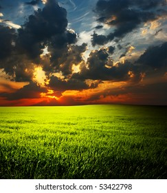Dramatic cloudy sunset over field with green grass