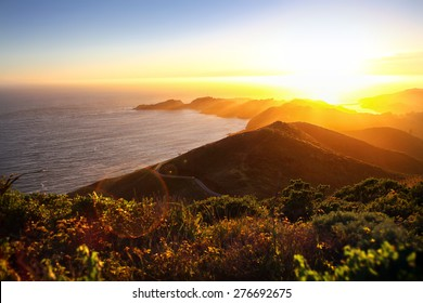Dramatic coastal sunset with island peninsula and golden light ocean