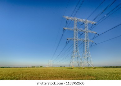 Dramatic colored rural Dutch landscape with high voltage pylons and lines against a blue sky. It is a sunny evening in summertime.