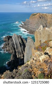 Dramatic and colorful cliffs on Alentejo West Coast at Cabo Sardao, Alentejo, Portugal, with white storks nesting at the top of the rocky cliffs