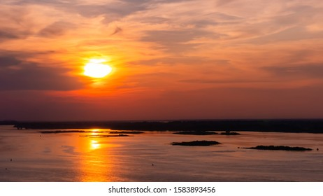 Dramatic colorful golden susnet with moving clouds on the Volga river. Evening time, warm illumination. Calm, peaceful, atmospheric view, relaxation concept