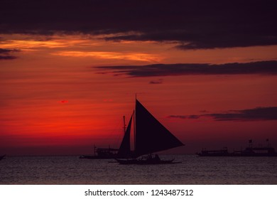 Dramatic colorful sea sunset with sailboat. Summer time. Travel to Philippines. Luxury tropical vacation. Boracay paradise island. Nature background. Seascape view. Tourism concept. Water transport